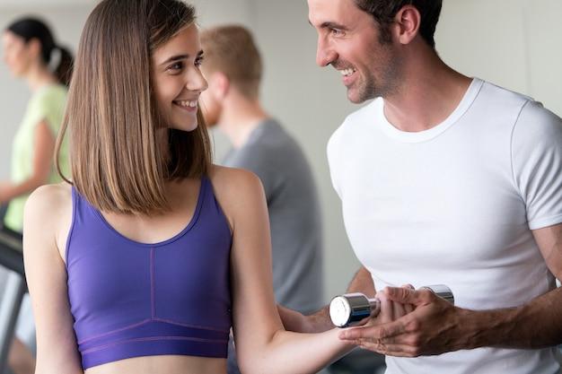 Fitness, sport, esercizio fisico e concetto di dieta. sorridente giovane donna e personal trainer con manubri in palestra