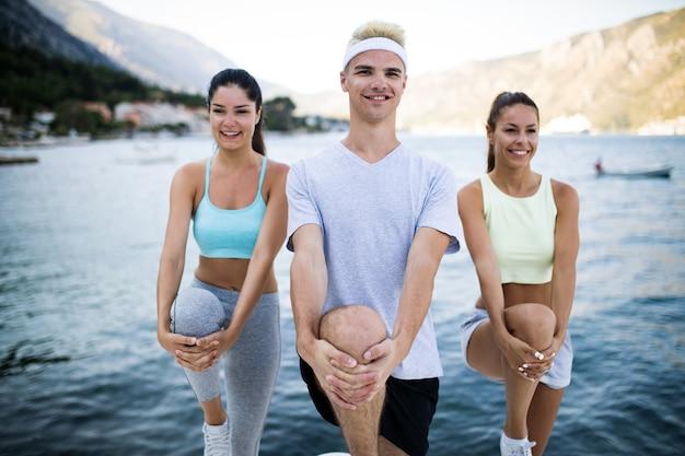 Fitness, sport, amicizia e concetto di stile di vita sano. gruppo di amici felici o sportivi che si esercitano e si allungano all'aperto