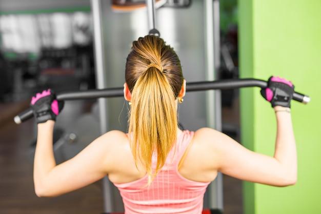 Forma fisica, sport, sollevamento pesi e concetto della gente - ragazza sportiva che sviluppa alcuni muscoli su un simulatore