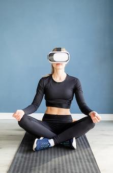 Fitness, sport e tecnologia. giovane donna atletica indossando occhiali per realtà virtuale facendo yoga sul tappetino fitness