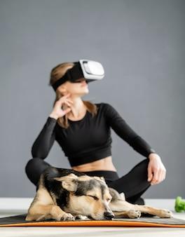 Fitness, sport e tecnologia. giovane donna atletica che indossa occhiali per realtà virtuale seduto sul tappetino fitness con il cane