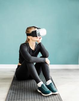 Fitness, sport e tecnologia. giovane donna atletica che indossa occhiali per realtà virtuale seduto sul tappetino fitness