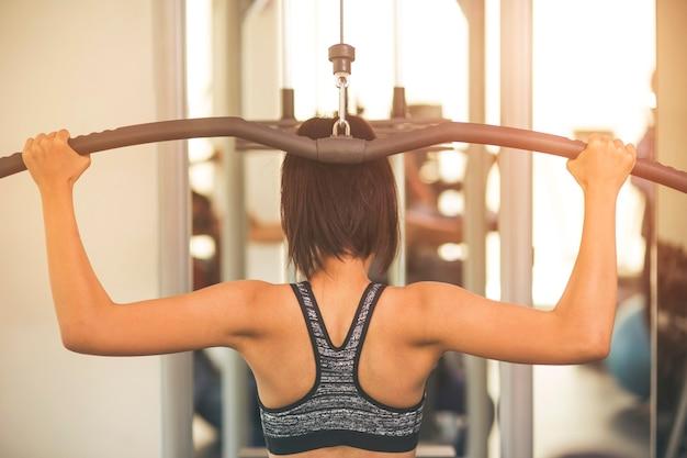 Concetto di fitness, sport, allenamento, palestra e stile di vita - gruppo di donne che excercising con le barre in palestra