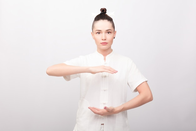 Concetto di fitness, sport, formazione e stile di vita - giovane donna che fa esercizio di yoga. giovane donna che pratica tai chi chuan in palestra. abilità di gestione cinese energia di qi.