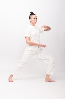 Concetto di fitness, sport, allenamento e stile di vita - giovane donna che fa esercizio di yoga. giovane donna che pratica tai chi chuan in palestra. l'energia di qi di abilità di gestione cinese.