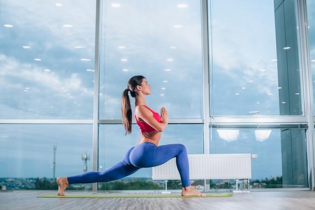 Concetto di fitness, sport, formazione e stile di vita - giovane donna che fa esercizi di yoga sul materassino yoga in palestra