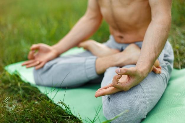 Fitness, sport, yoga e concetto di stile di vita sano - close up di persone che meditano in posizione seduta facile nel parco o in giardino