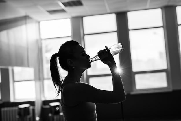 Siluetta sportiva della ragazza di forma fisica che excercising e che beve un'acqua