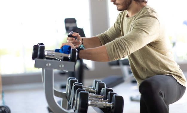 Personale di fitness pulizia macchine per esercizi con spray disinfettante alcolico in palestra