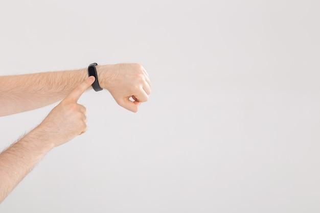 Concetto di fitness e tecnologia - tracker di attività su un polso maschile su sfondo bianco copia spazio.