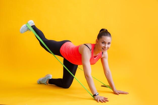 Un istruttore di fitness fa un esercizio per i glutei con un elastico