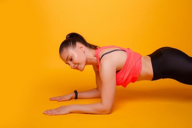 Istruttore di forma fisica che fa un esercizio della plancia