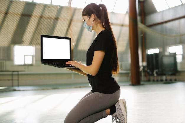 Istruttore di fitness inginocchiarsi in palestra vuota donna in maschera medica lavora in remoto al coperto in solitudine si siede con il computer portatile sulle ginocchia quarantena di blocco del coronavirus covid autoisolamento