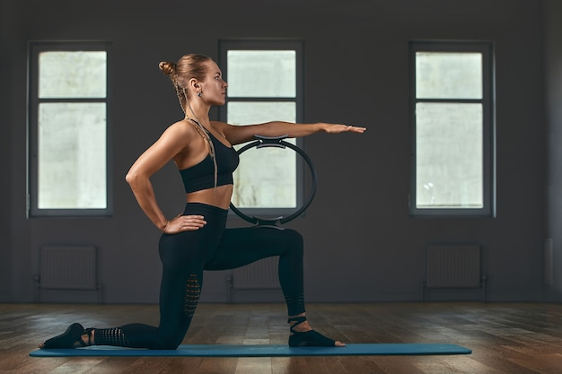L'istruttore di fitness mostra gli esercizi con un espansore ad anello mattina nella sala fitness