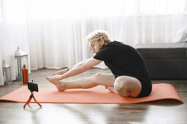 Istruttore di fitness o video blogger che fa stretching. l'uomo si sta riprendendo con la fotocamera dello smartphone a casa.