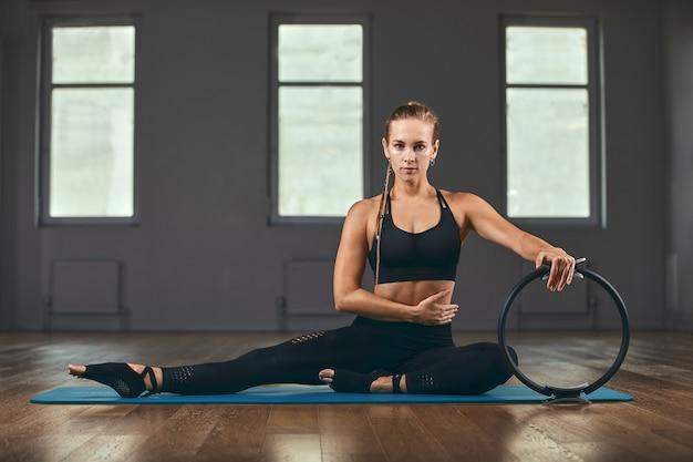 Istruttore di fitness con una bella figura posa per la fotocamera durante un allenamento in palestra con un anello ispander.