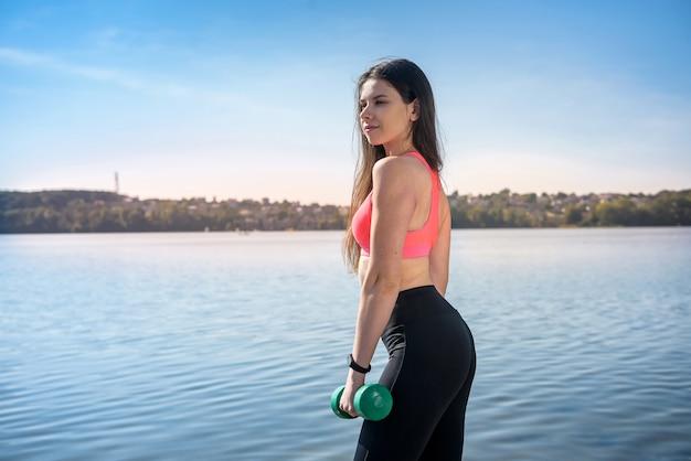 Allenamento fitness - esercizio di lavoro di bella giovane donna con manubri, come parte del suo stile di vita.