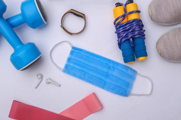 Allenamento fitness durante il periodo covid-19. composizione piatta di attrezzatura fitness, accessori, maschera medica su sfondo bianco. concetto di stile di vita sano. vista dall'alto