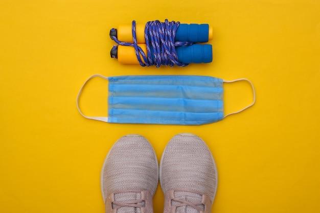 Allenamento fitness durante il periodo covid-19. composizione piatta di scarpe da ginnastica, corda per saltare, maschera medica su sfondo giallo. concetto di stile di vita sano. vista dall'alto