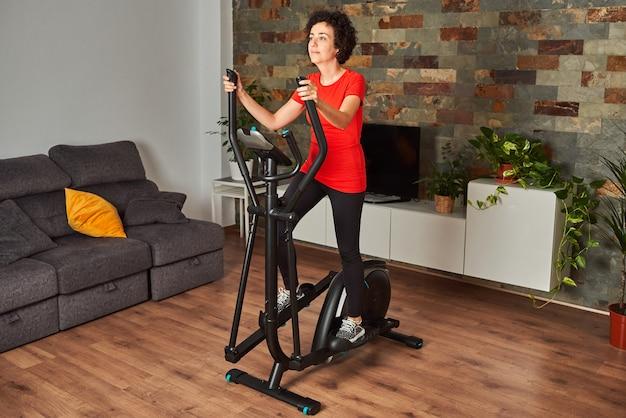 Allenamento fitness donna a casa allenamento su smart cross trainer ellittico al chiuso