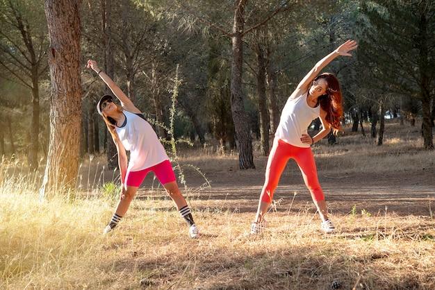 Fitness. due corridori femminili che allungano le gambe all'aperto nel parco in estate