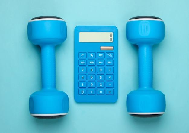 Fitness, perdita di peso ancora in vita. conteggio calorie. calcolatrice e manubri su pastello blu
