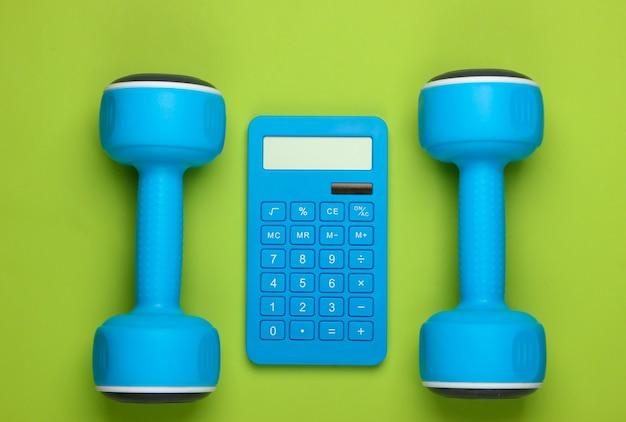 Fitness, perdita di peso ancora in vita. conteggio calorie. calcolatrice e manubri sul verde. minimalismo. lay piatto