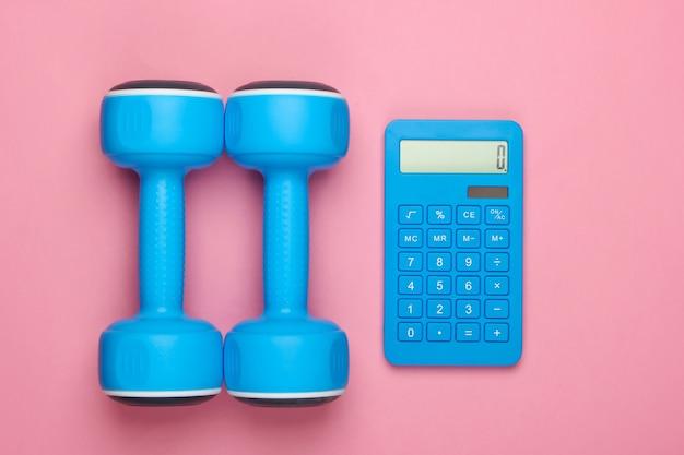 Fitness, perdita di peso ancora in vita. conteggio calorie. calcolatrice e manubri su un pastello rosa