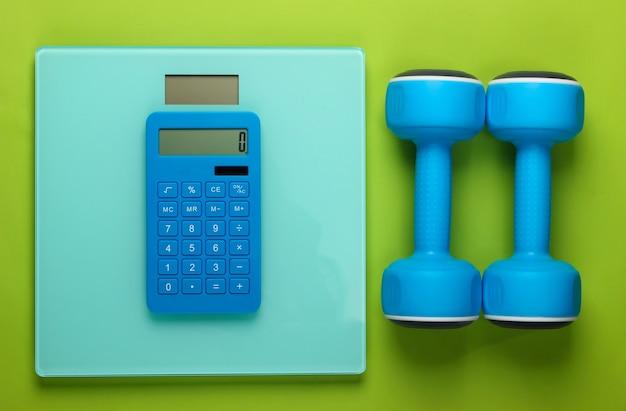 Fitness, perdita di peso ancora in vita. conteggio calorie. calcolatrice, manubri e scale sul verde. minimalismo. lay piatto