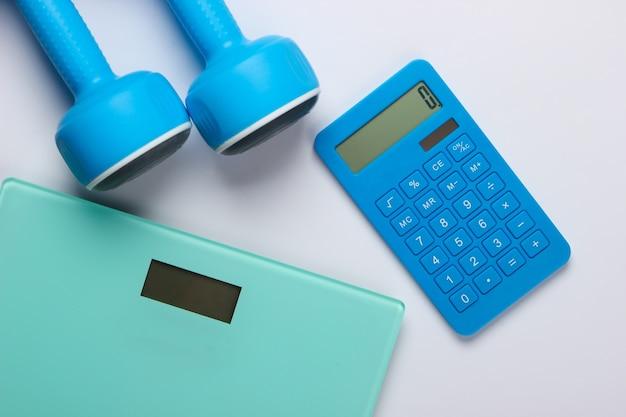 Fitness, perdita di peso ancora in vita. conteggio calorie. calcolatrice, manubri e scale su bianco. minimalismo. lay piatto