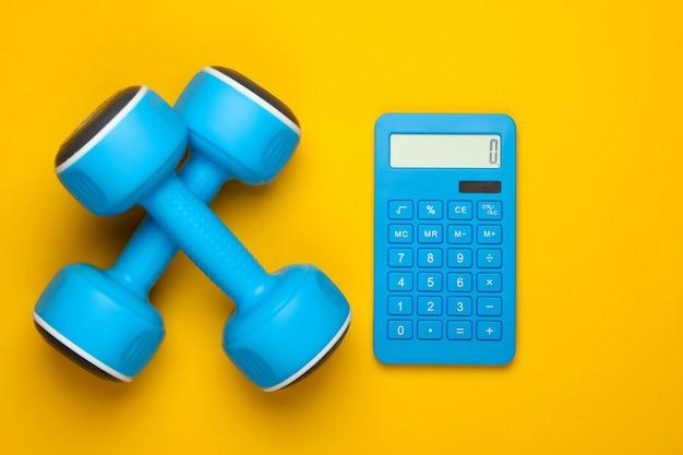 Fitness, perdita di peso ancora in vita. conteggio calorie. calcolatrice e manubri su colore giallo. minimalismo. lay piatto