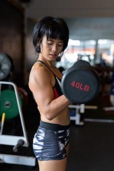 Donna di forma fisica che fa ragazza bicipite con manubri in palestra