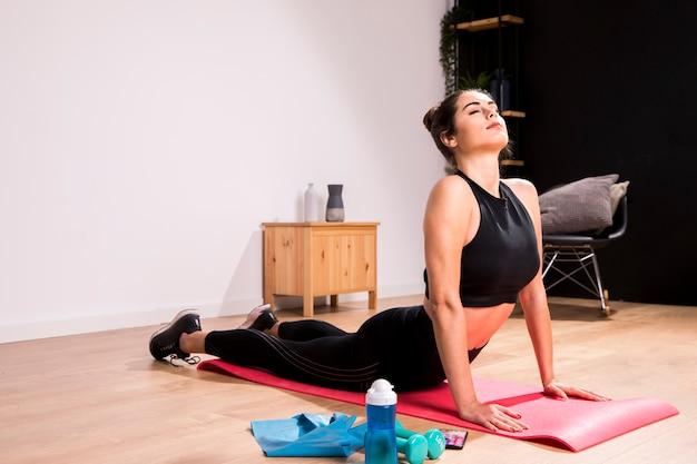 Donna di forma fisica che fa esercizio a casa Foto Premium