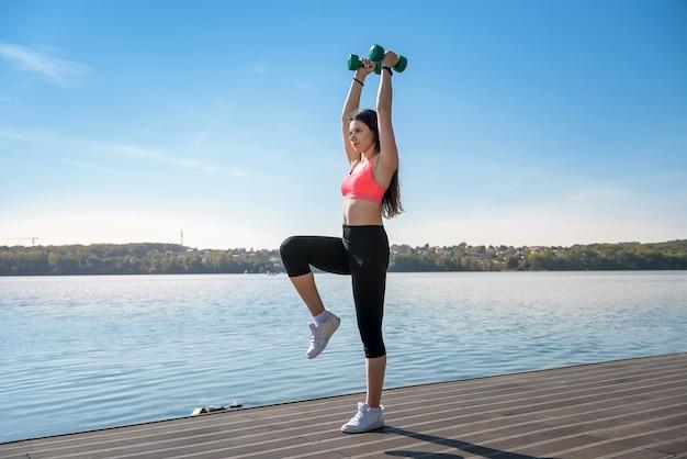 Donna fitness che fa esercizio mattutino con piccoli pesi del lago of