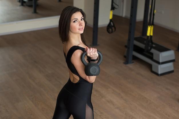 Donna di forma fisica che fa esercizio di oscillazione della stampa della spalla con un kettlebell