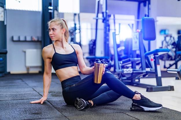 Acqua potabile della donna di forma fisica. ragazza atletica che si siede e che riposa sul pavimento in palestra. donna che si siede nella posa di yoga che riposa.