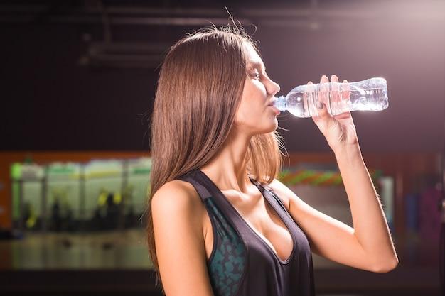 Acqua potabile della donna di forma fisica dalla bottiglia. giovane femmina muscolare in palestra prendendo una pausa dall'allenamento.
