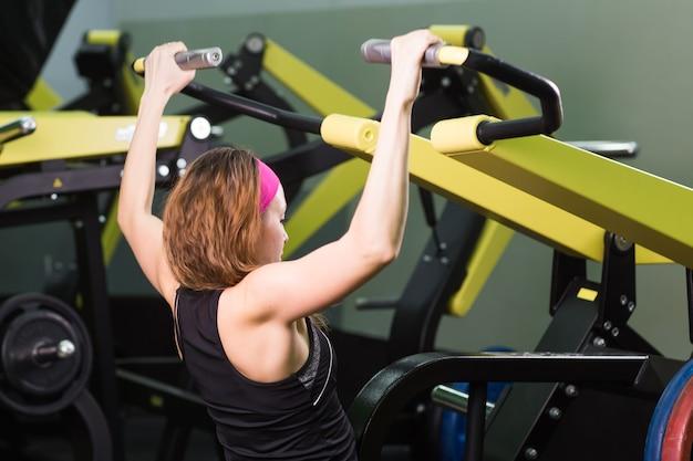 Donna fitness eseguire esercizio con macchina ginnica in palestra