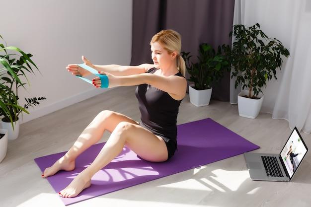Donna fitness che si esercita sul pavimento a casa e guarda video di fitness sul laptop