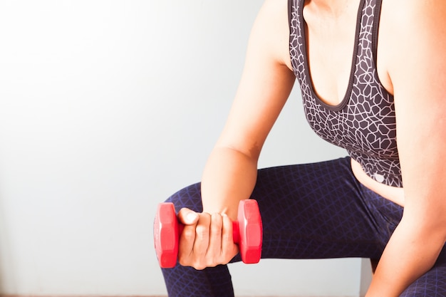Fitness donna con dumbbell rosso, allenamento e sano