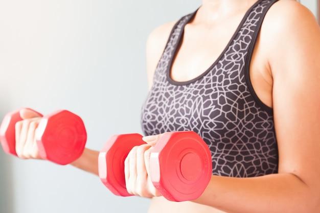 Fitness donna con dumbbells rossi, allenamento e sano