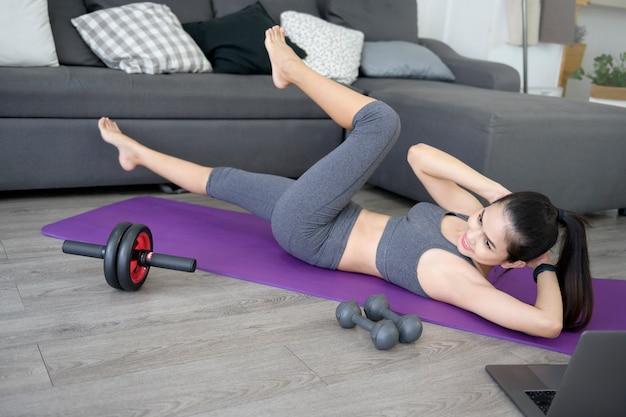 La donna di forma fisica sta facendo l'allenamento degli addominali con l'esercizio degli scricchiolii su una stuoia, uno stile di vita sano e un concetto di sport