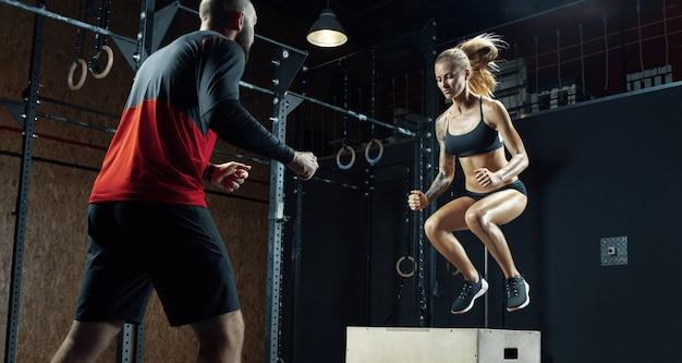 La donna fitness sta facendo esercizi con l'aiuto di un personal trainer in una palestra moderna