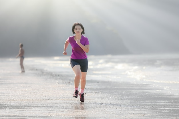 Fitness donna sta correndo su ao nang beach krabi thailand
