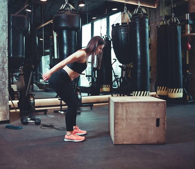Donna di forma fisica che salta sull'addestramento della scatola di legno alla palestra