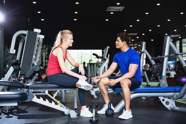 Fitness donna e uomo si siedono e parlano dopo l'esercizio in palestra