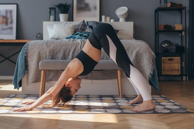 Donna di forma fisica che pratica posa di yoga del cane rivolto verso il basso.