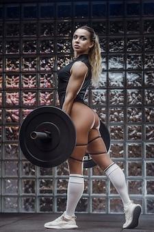 Donna di forma fisica che pompa i muscoli delle gambe di culo culo bottino