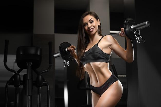 Donna fitness pompare i muscoli allenamento addominali, braccia, schiena, torace busto esercizi in palestra