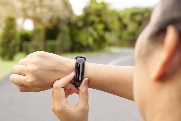 Corridore della donna di forma fisica che installa orologio astuto prima della corsa.
